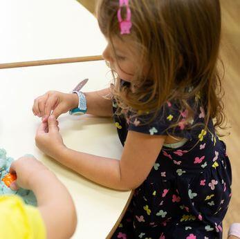 Maedchen spielt mit Knetmassse im Kindergarten